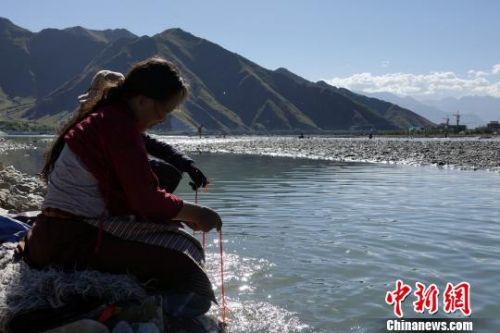 60岁的藏族老人巴金在河水中清洗法器。 孙翔 摄